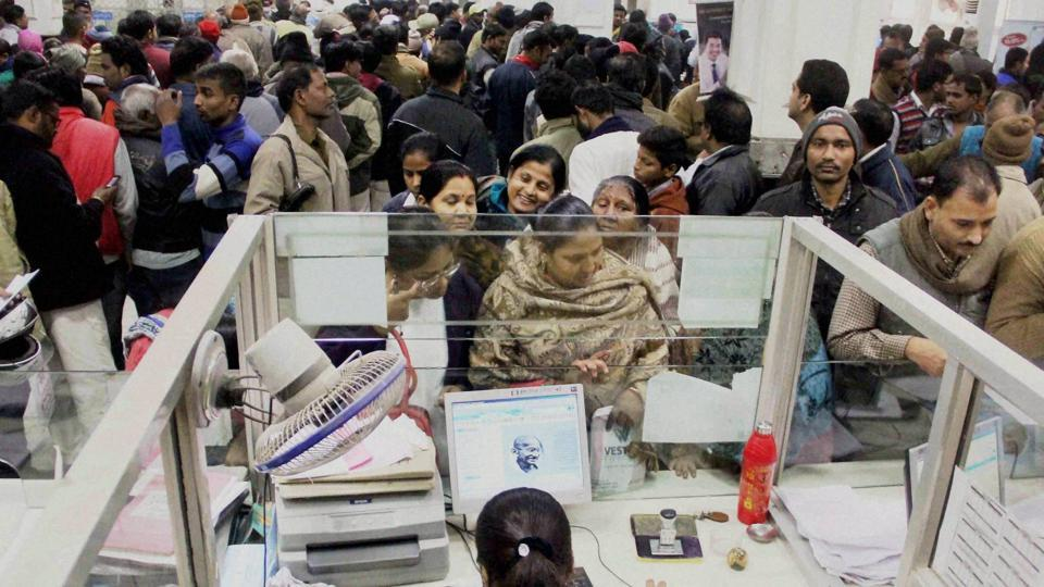 People stand in long queues to deposit and withdraw cash at a bank in Allahabad on Tuesday.