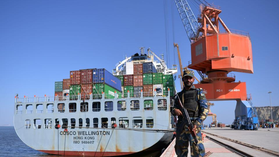 A Pakistani Naval personnel stands guard near a ship carrying containers at the Gwadar port during the opening ceremony of a pilot trade programme between Pakistan and China.