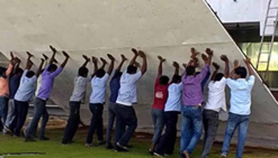 Groundsmen put up the sight screen at the MA Chidambaram Stadium in Chennai on Wednesday