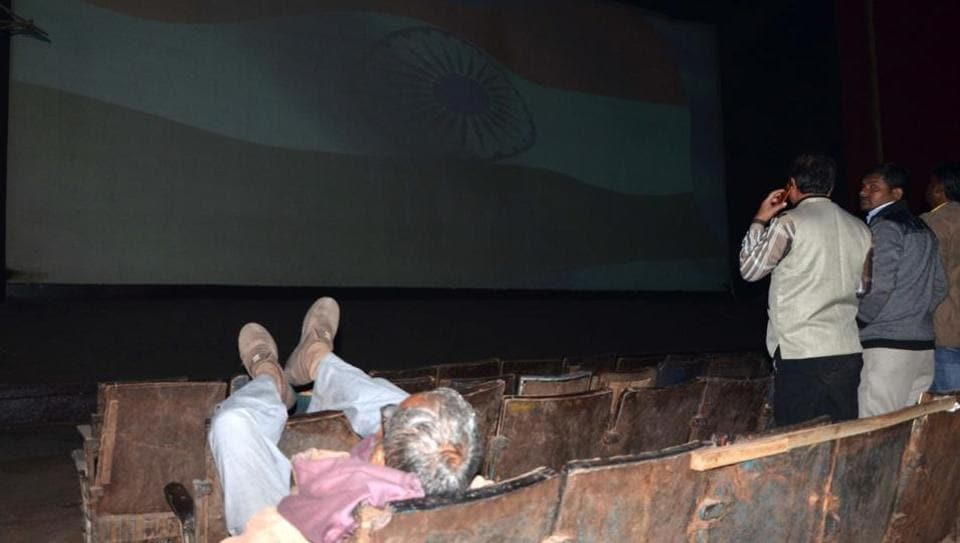 An old man sleeps with his feet up as the national anthem is played at Prasad Cinema hall in Bareilly.