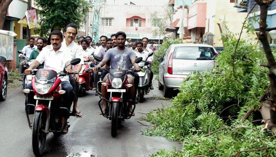 DMK treasurer and Tamil Nadu opposition leader MK Stalin ride pillion on a two-wheeler to visit Cyclone Vardah-affected areas in his Kolathur Assembly constituency in Chennai on Tuesday.