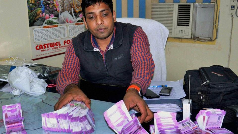 Police showing Rs 27 lakh in new currency notes recovered from four accused in Faridabad on December 13.