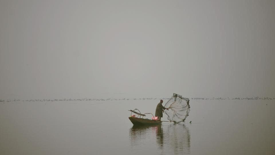 A fisherman casts his net from his boat during dense fog on Dal Lake in Srinagar on December 7, 2016. (AFP)