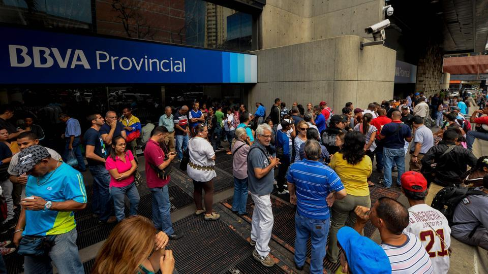 People queue outside a bank in Caracas in an attempt to deposit money, on December 13, 2016. Venezuelan President Nicolas Maduro signed an emergency decree removing Venezuela's largest bank note, the 100 bolivar bill, from circulation because of what he called a Washington-sponsored plot against his country's troubled economy.