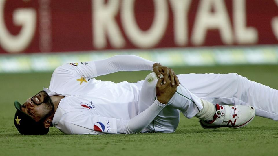Pakistan's Mohammad Amir reacts after injuring his knee while fielding during play on day one of the first cricket test between Australia and Pakistan in Brisbane.