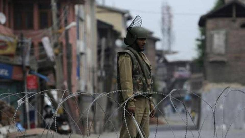 A paramilitary soldier stands guard near a barricade during curfew in Srinagar in July 2016, days after militant commander Burhan Wani  was killed in an encounter.