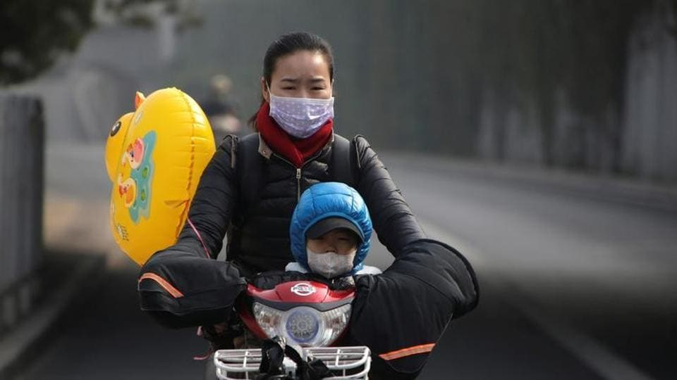 A woman and her son wearing masks ride an electric bicycle on a hazy day in Beijing.