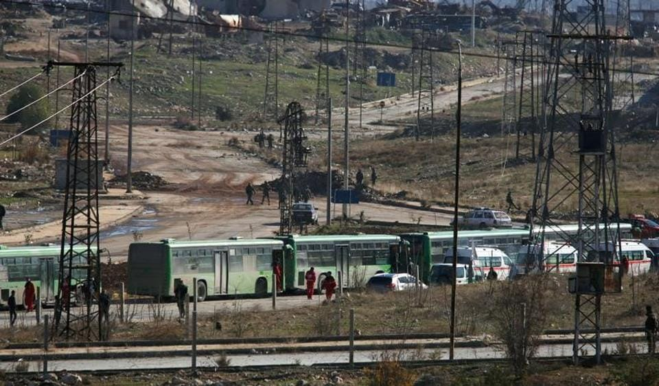 Buses and ambulances wait to evacuate civilians and rebels from eastern Aleppo.