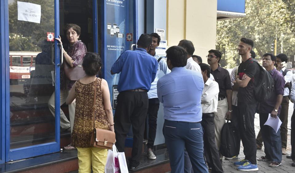 People wait outside a bank in Colaba in Mumbai.