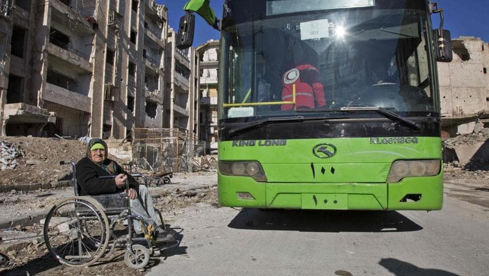 An elderly Syrian woman in a wheelchair waits next to a bus during an evacuation operation of rebel fighters and their families from rebel-held neighbourhoods in the embattled city of Aleppo on Thursday.