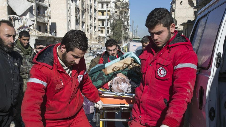 Staff of the Syrian Red Crescent pull a stretcher with a wounded person in the embattled city of Aleppo on December 15, 2016. A bomb explosion reportedly occurred near a Red Crescent centre in Homs city, central Syria.