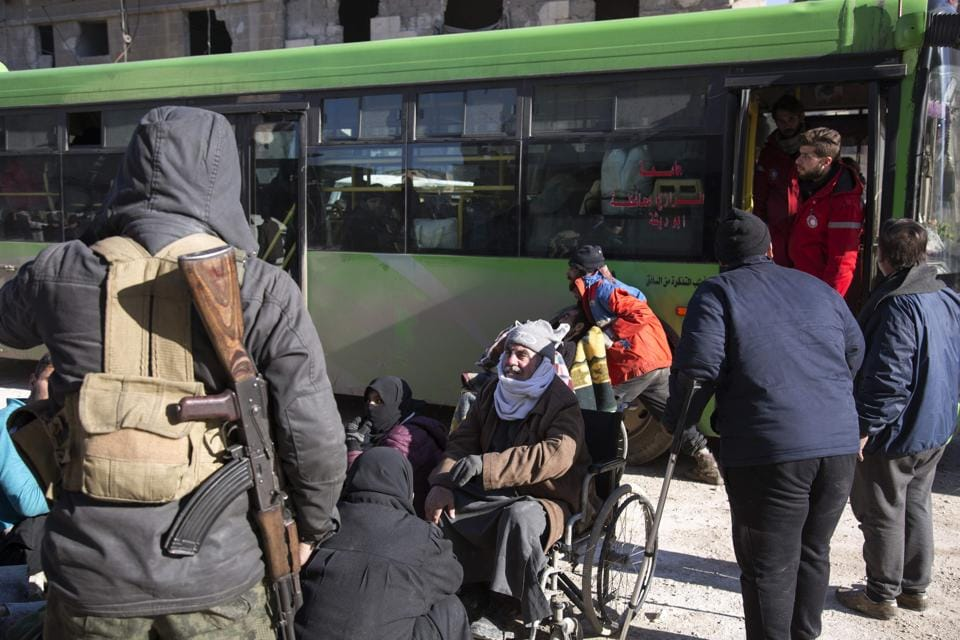 Syrians gather during the evacuation A convoy of ambulances and buses left rebel territory in Aleppo in the first evacuations under a deal for opposition fighters to leave the city after years of fighting.  (AFP)