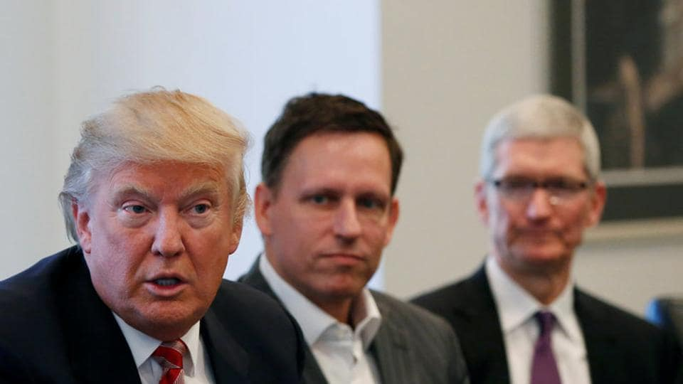 US president-elect Donald Trump speaks as PayPal co-founder and Facebook board member Peter Thiel (centre), and Apple Inc CEO Tim Cook (right)look on during a meeting with technology leaders at Trump Tower in New York.
