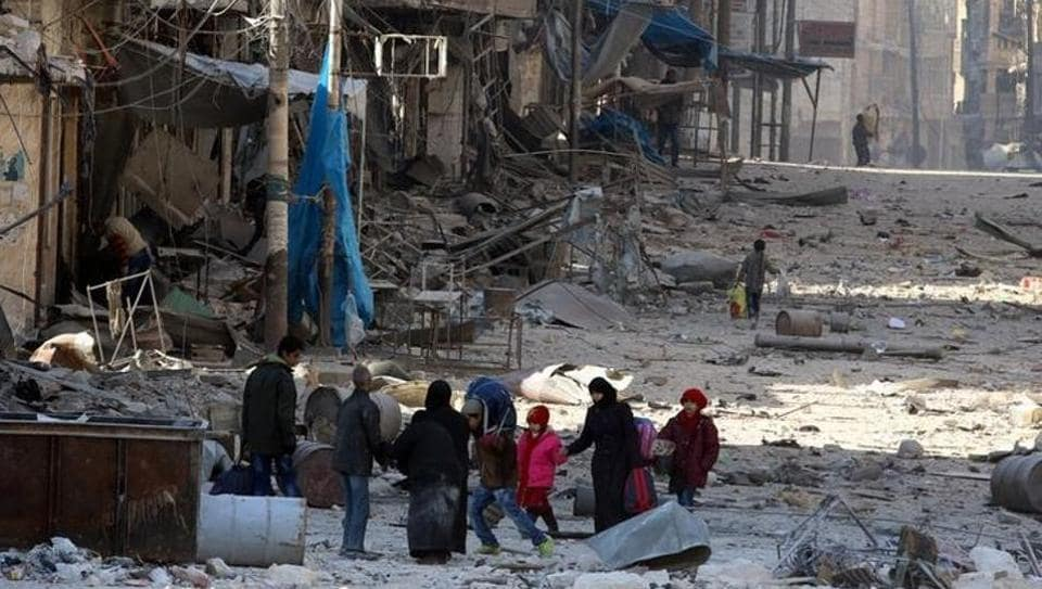 Syrians walk over rubble of damaged buildings, while carrying their belongings, as they flee clashes between government forces and rebels in Tariq al-Bab and al-Sakhour neighborhoods of eastern Aleppo towards other rebel held besieged areas of Aleppo.