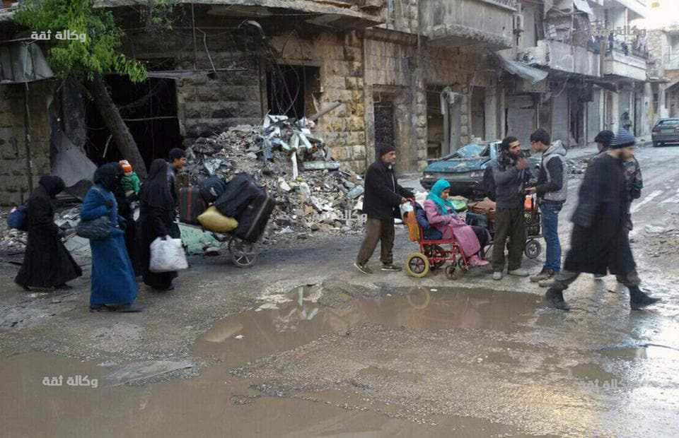This image released by the Thiqa News Agency, shows civilians gathering for evacuation from eastern Aleppo. (AP)