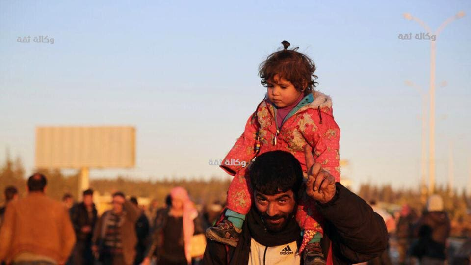 This image released by the Thiqa News Agency, shows a Syrian man carrying his daughter as they are evacuated from eastern Aleppo.