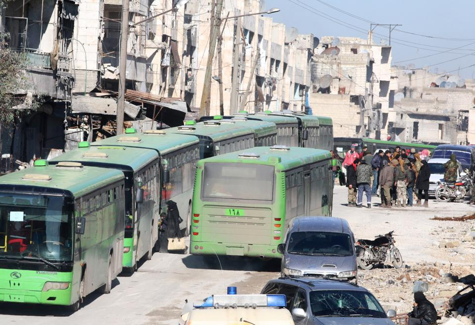People get on buses to be evacuated from al-Sukkari rebel-held sector of eastern Aleppo on Thursday.  (REUTERS)