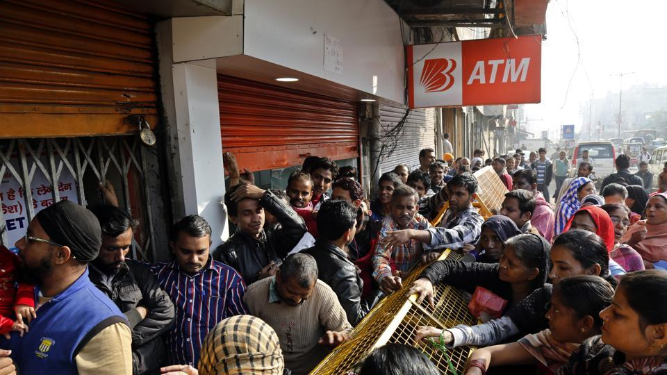 People line up outside a bank in Delhi as the recall of high-value banknotes has left the country short of cash.
