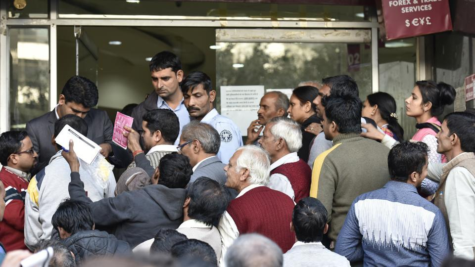 People wait in a queue outside Axis Bank at Stateman Building branch in Connaught Place to deposit and withdraw money.