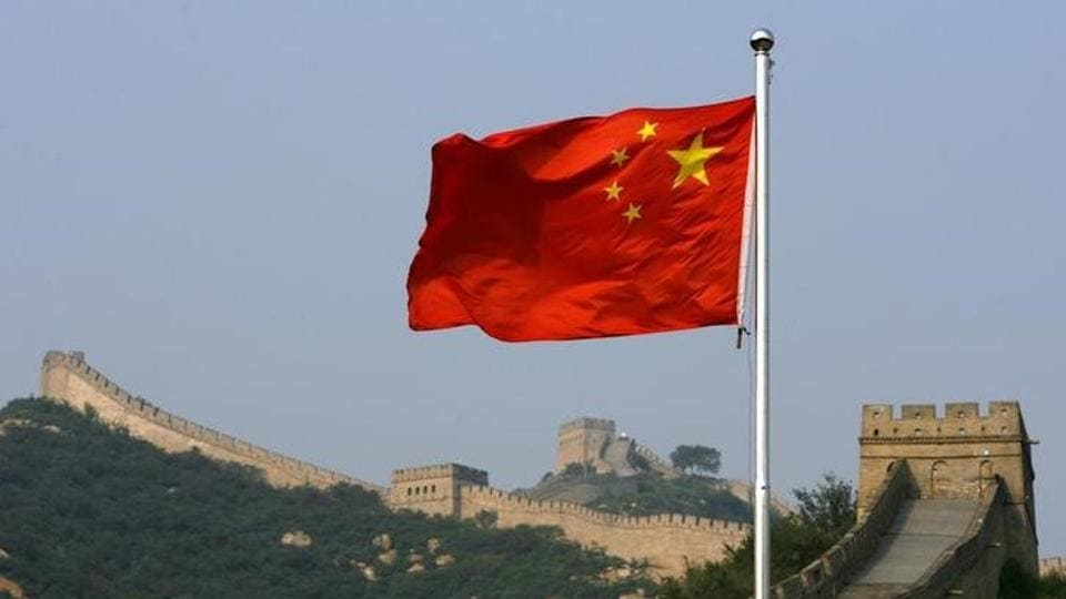 A Chinese flag flies in front of the Great Wall of China.