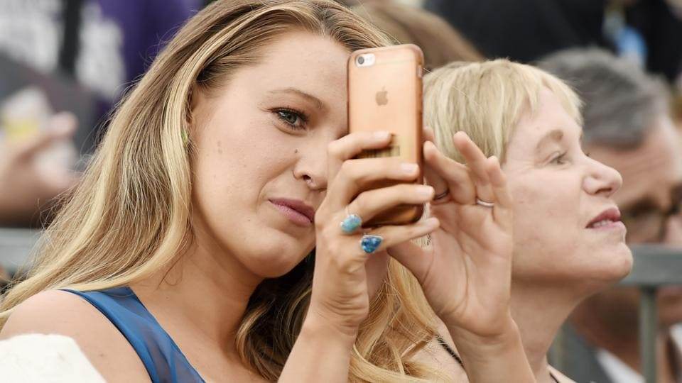 Actress Blake Lively points her iPhone at photographers during a ceremony. (Chris Pizzello/Invision/AP)