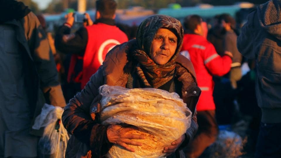 An evacuee from rebel-held east Aleppo carries bread upon her arrival with others at the town of al-Rashideen, which is held by insurgents, Syria.