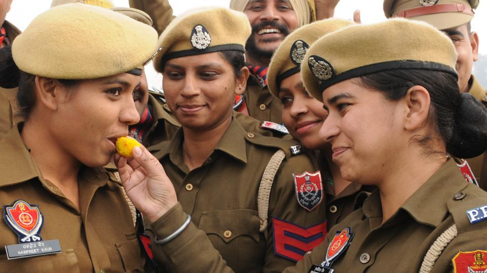 Women constables offering sweets to each other after their promotion during pipping ceremony in Jalandhar on Thursday.