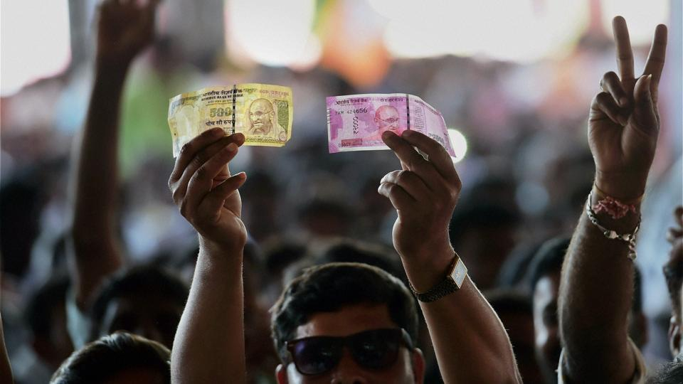 A BJP supporter shows a demonetised Rs 500 currency note and a new Rs 2000 currency note  in Bengaluru on Sunday.