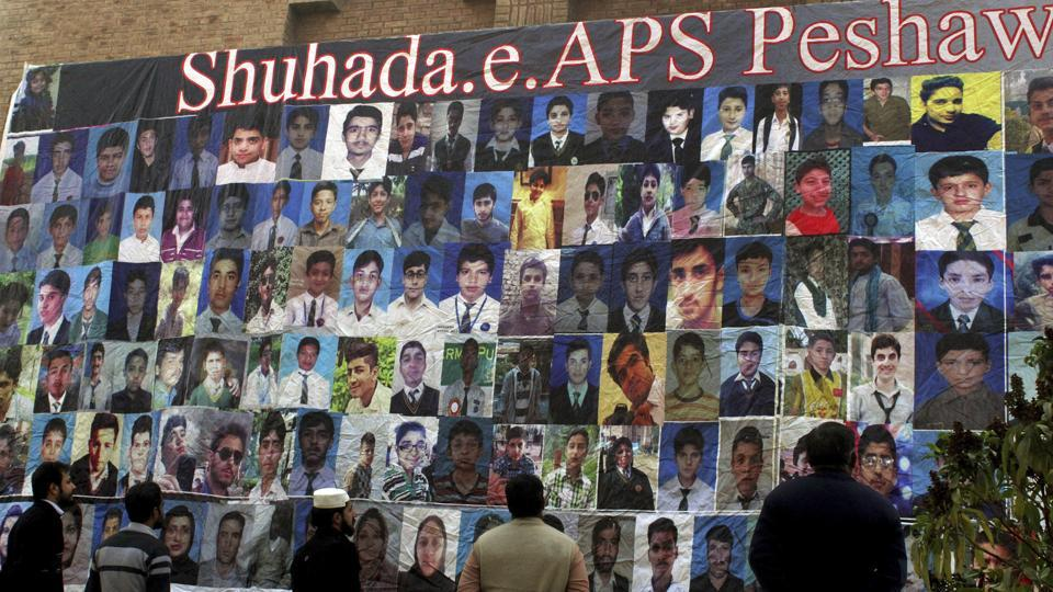 Pakistanis look at a banner displaying pictures of victims of an attack on a Peshawar school in 2014, installed by authorities in connection with the second anniversary of the attack, in Peshawar, Pakistan.