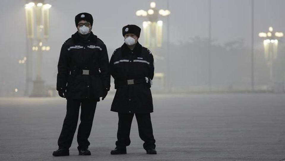 Policemen wear protective masks at the Tiananmen Square on an extremely polluted day as hazardous, choking smog continues to blanket Beijing, China on December 1.