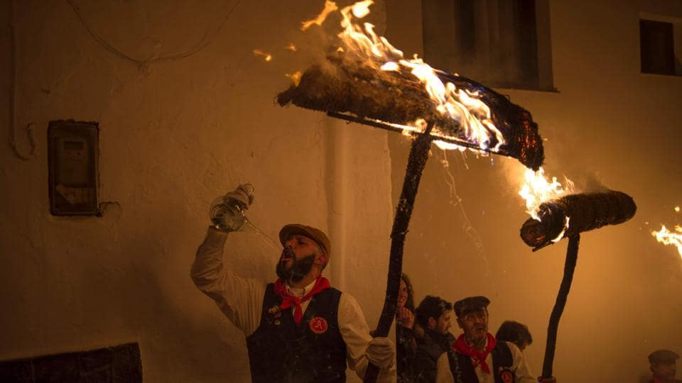 Men drink anisette and hold burning rondeles during the procession to mark the feast of Saint Lucia. (AFP)