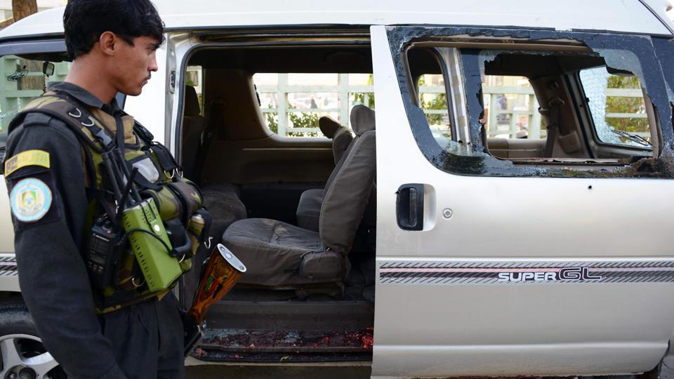 An Afghan policeman inspects a damaged vehicle in Kandahar in which five female airport workers were killed on Saturday.