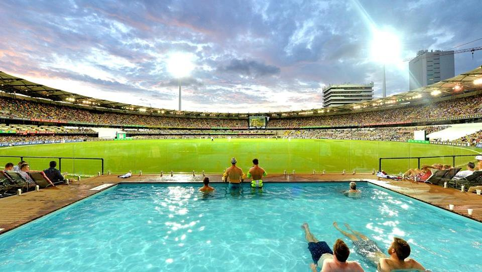 Fans watch the cricket from the pool as the sun sets during day two of the first Test match between Australia and Pakistan at The Gabba on December 16, 2016 in Brisbane.