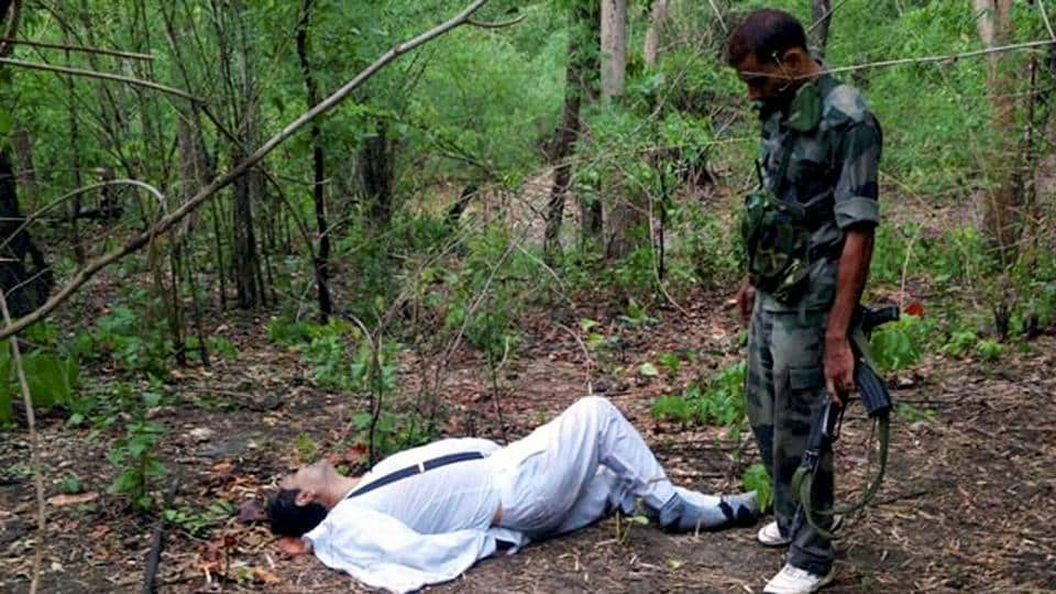 A security personnel stands near the body of one of the victims of Maoist attack in a densely forested area in Bastar, about 345 kilometers (215 miles) south of Raipur, Chhattisgarh.