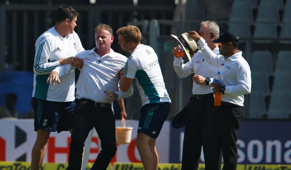 Umpire Paul Reiffel being helped by support staff after a throw from India's Bhuvneshwar Kumar hit him on the head during the fourth India-England Test.
