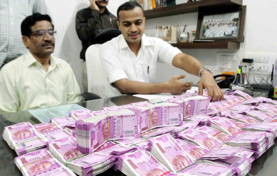 Crime branch police displays seized currency of rupees one crore and forty thousand in new notes in Thane on Wednesday.