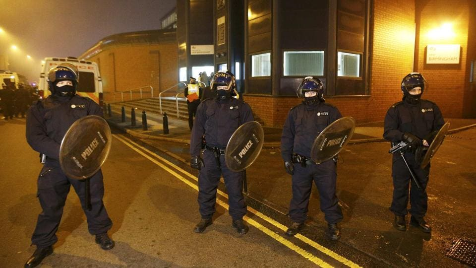 Police officers in riot gear stand outside Winson Green prison, run by security firm G4S, after a serious disturbance broke out, in Birmingham, Britain.