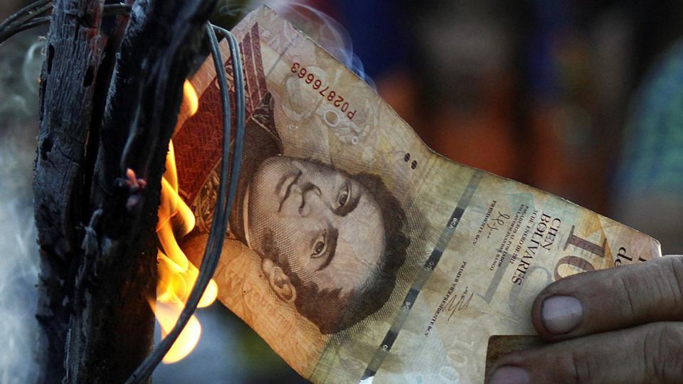 A man burns a 100-bolivar bill during a protest in El Pinal, Venezuela.