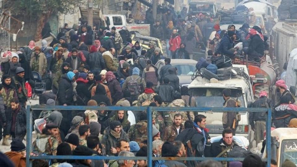 Rebel fighters and civilians gather as they wait to be evacuated from a rebel-held sector of eastern Aleppo, Syria December 16, 2016.