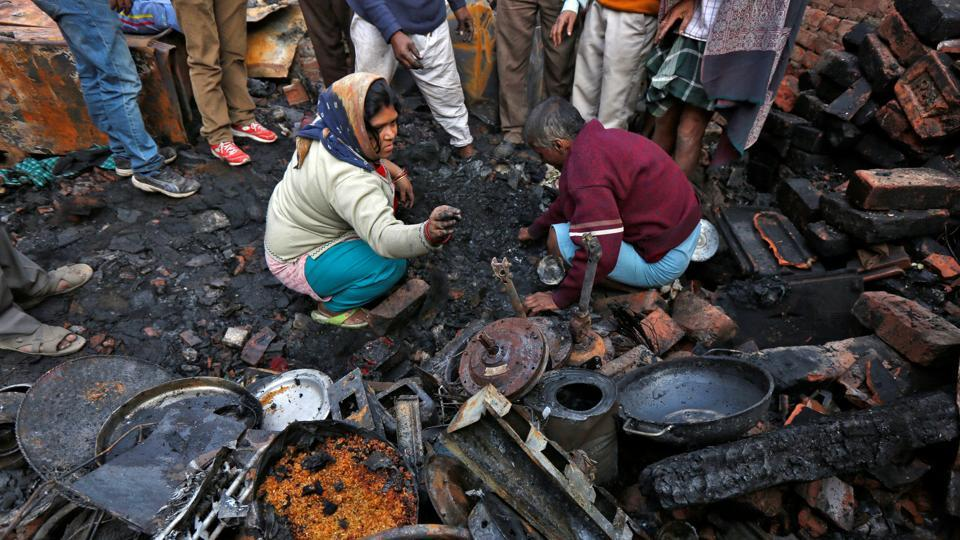 A woman sifts through the remains of her house gutted by a fire in a slum area in the wee hours in Kolkata on Saturday.