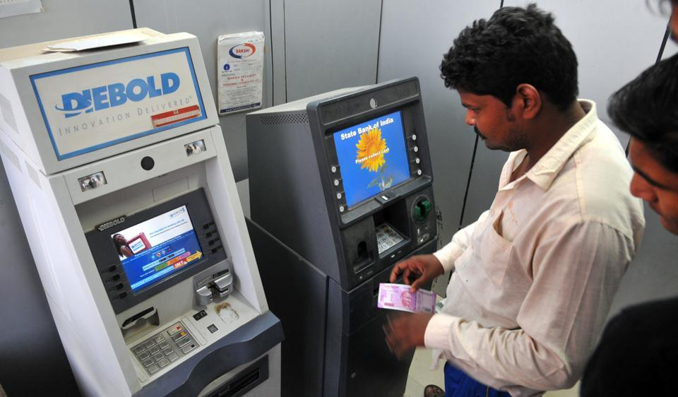 A man takes out Rs 2000 currency note from an ATM in Indore on Friday.