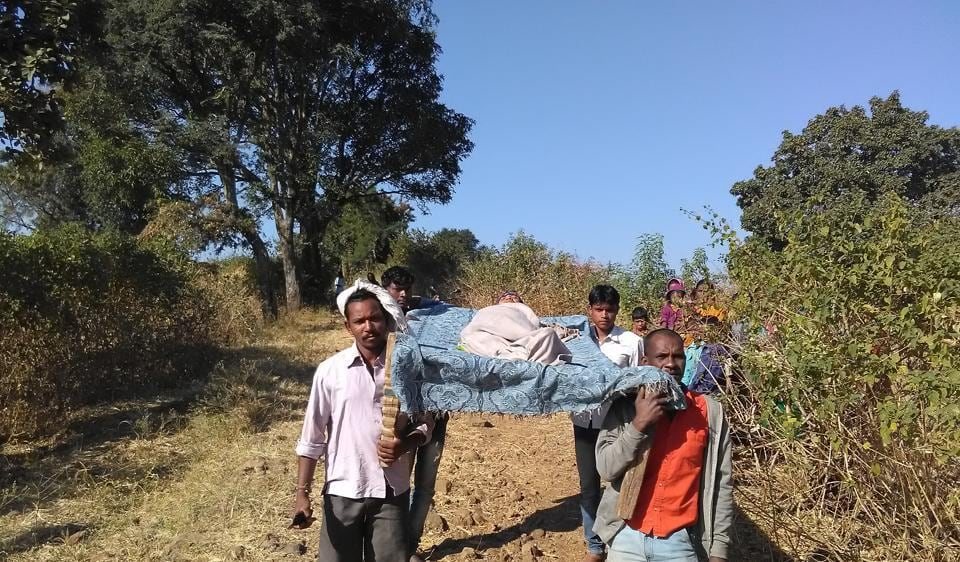 Villagers carry an ailing 78-year-old woman on a cot after 108 ambulance failed to reach Salaidhana village in Betul district.