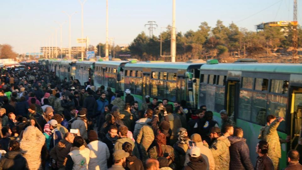 Residents gathered near green government buses for evacuation in eastern Aleppo, Syria.