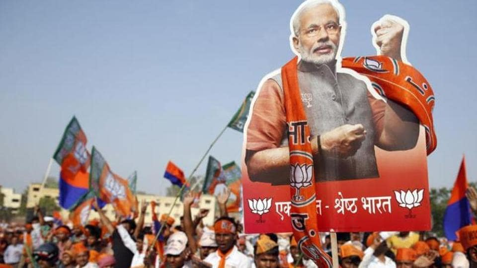 A supporter of Bharatiya Janata Party holds up a cutout of the party's prime ministerial candidate Narendra Modi during an election campaign rally in Varanasi, in Uttar Pradesh.