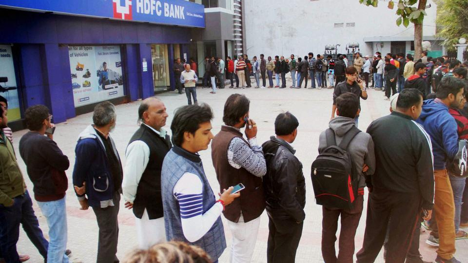 People stand in a long queue to withdraw currency notes at an ATM in Allahabad on Friday.