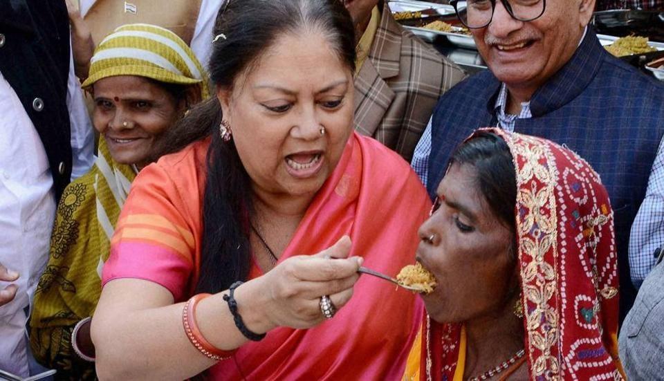Rajasthan chief minister Vasundhara Raje shares food with a woman during the launch of 'Annapurana Rasoi Yojana , in Jaipur on Thursday.