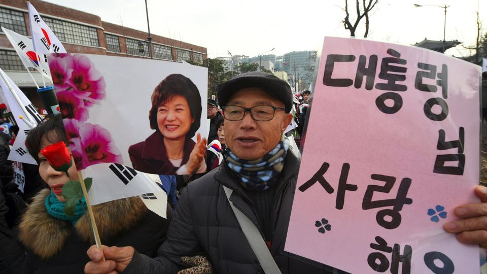 A Supporter of South Korea's President Park Geun-Hye holds banners showing a portrait of Park and reading