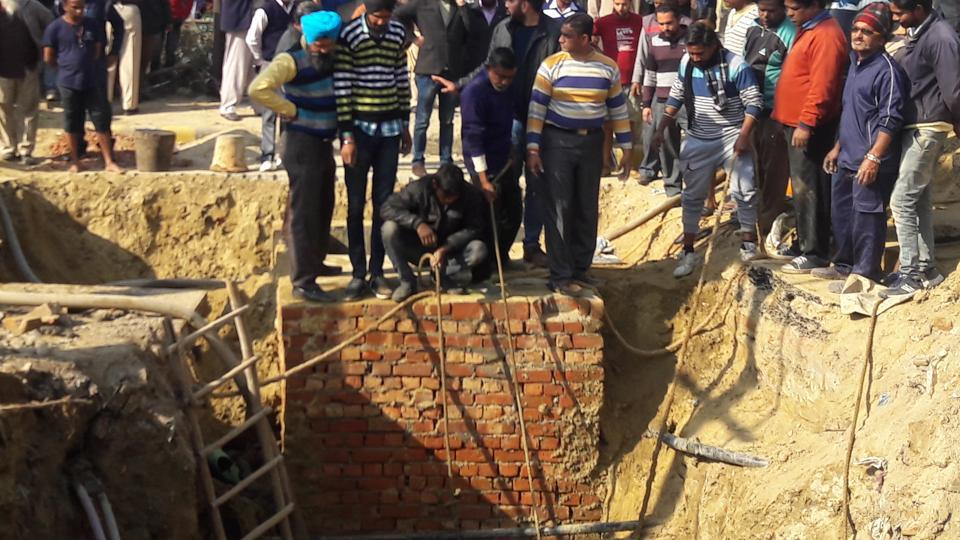 Workers trying to bring out the body of the labourer in Jalandhar on Saturday.