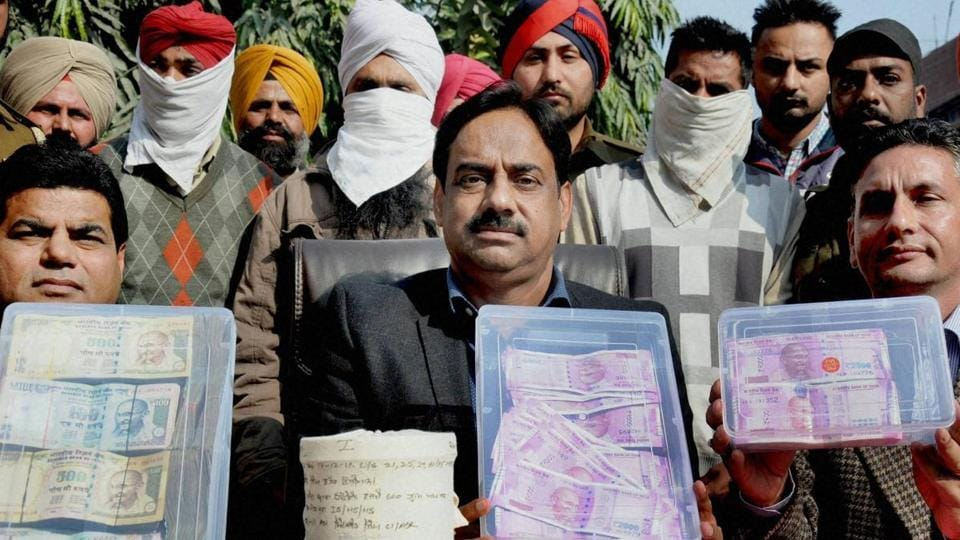 Counter Intelligence Officials showing the accused Karaj Singh, Malkeet Singh and Jaswinder Singh to the media who were arrested with 600 gm heroin and Rs 15 lakh in new and old currency notes in Amritsar on Sunday.