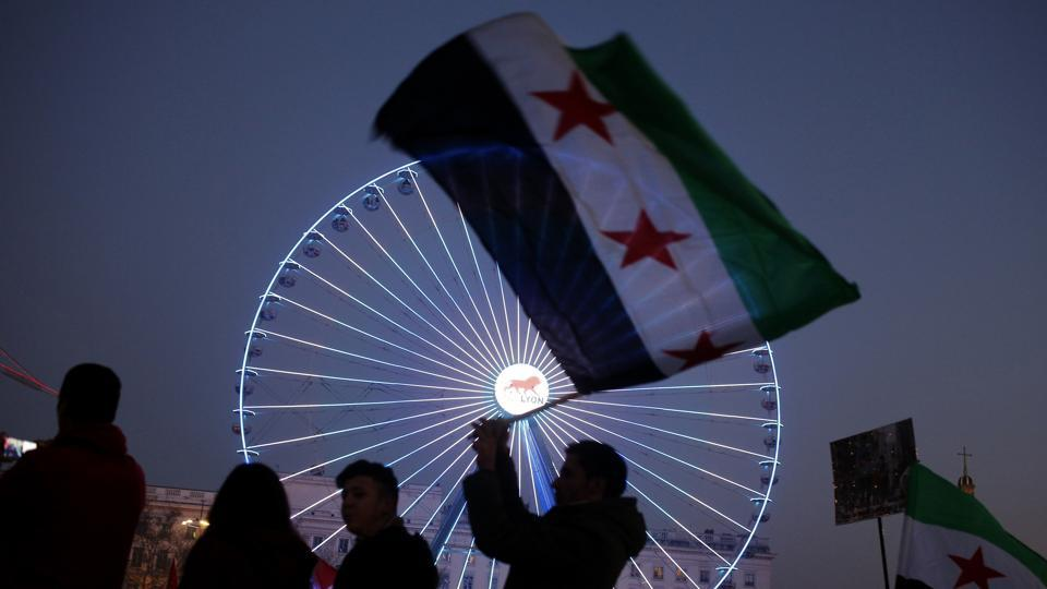 A man waves a Syrian flag during a gathering to protest against the war and the humanitarian crisis in Aleppo, in Lyon, central France. (Laurent Cipiani/AP Photo)